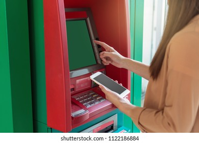 woman using the smart mobile phone for withdrawing in front of the ATM, business Automatic Teller Machine concept