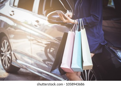 Woman are using smart phone after shopping in the mall  and standing in car park