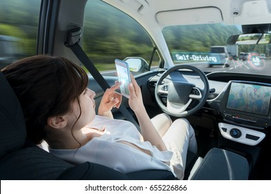woman using smart phone in autonomous car. self driving vehicle. autopilot. automotive technology.