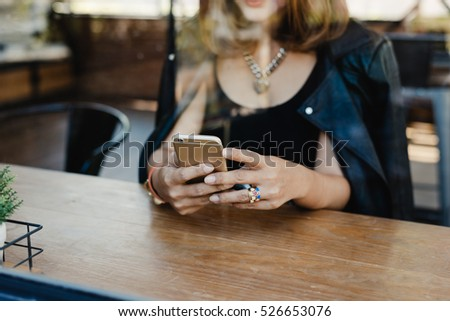 Woman using smart phone in a cafe,image of young woman sitting at a table with a coffee using mobile phone.