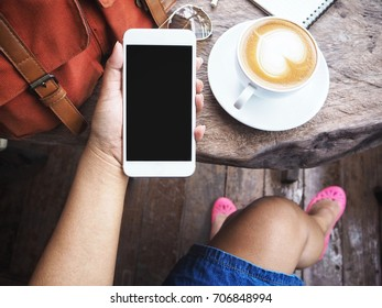 Woman using smart phone and coffee cup with bag