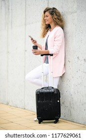 Woman using smart phone and holding coffee to go while leaning on the wall. Luggage next to her.