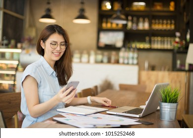 woman using smart phone and laptop in cafe.