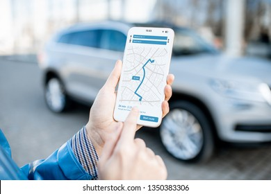 Woman using smart phone with navigation app, close-up view with modern car on the background