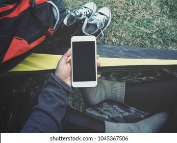 Woman using smart phone on hand at tent camping