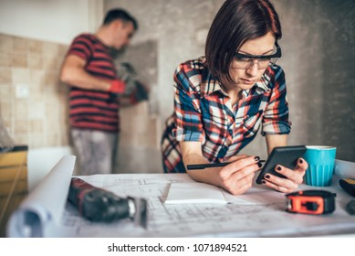 Woman using smart phone on the table while her husband removing old wall tiles in the kitchen