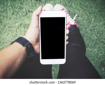 Woman using smart phone on hand and red sneakers