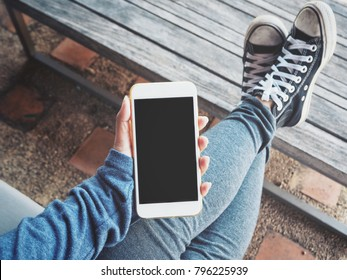 Woman using smart phone on hand with shoes