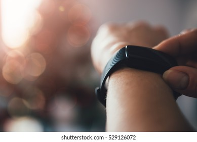 Woman using smart watch with a christmas tree in the background