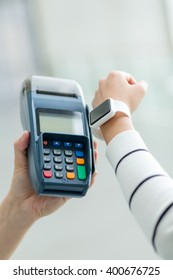 Woman using smart watch to settle the bill