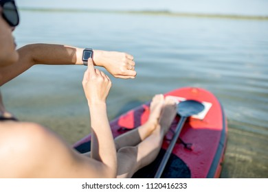Woman using smart watch while paddleboarding on the lake during the summer vacations
