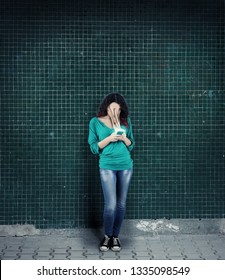 Woman using smartphone against a wall. The concept of phone addiction. Face absorbed by the phone.