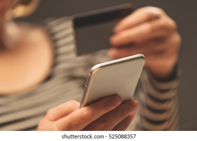 Woman using smartphone app to check e-wallet account balance, close up of hands with mobile phone and plastic credit card.
