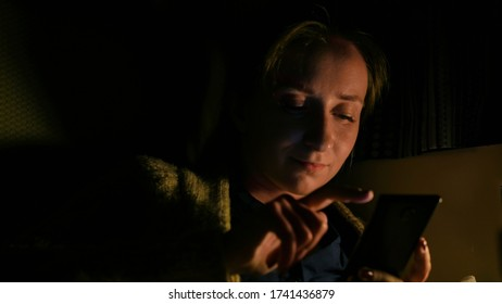 Woman using smartphone in cabin of cruise ship. Evening time, lowlight. Technology and journey concept