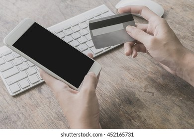 woman using smartphone and computer to online shopping and pay by credit card, Low light, selective focus on hand, can be used for e-commerce, business, technology and internet concept, Vintage tone