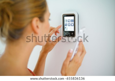 Woman using smartphone to control home connectivity interface