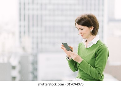 Woman using a smartphone in office by the window overlooking the business district with skyscrapers