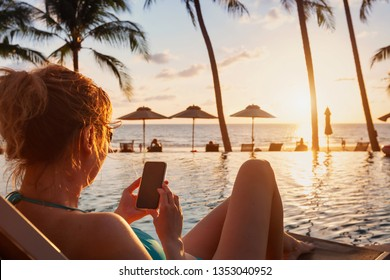 woman using smartphone on beach luxury hotel near swimming pool, travel app for tourist on mobile phone