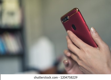 woman using smartphone on bed at home