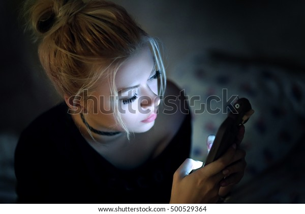 Woman using smartphone on bed at night