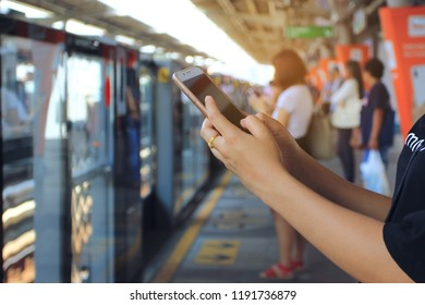 Woman using a smartphone on BTS sky train in bangkok background,thailand, Communication technology concept