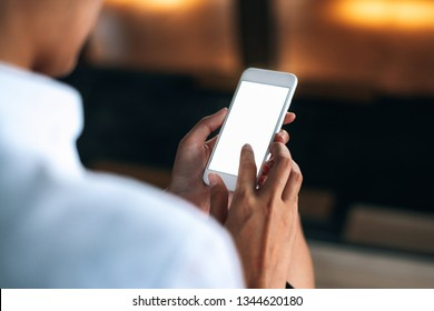 Woman using a smartphone read and text messages with blank space screen display from behind view- woman office worker- digital and communication concept