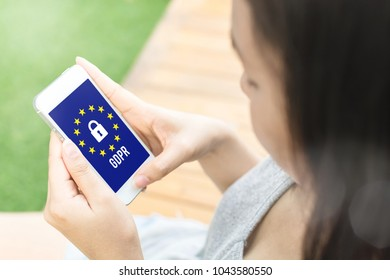 Woman using smartphone screen device show sign general data protection regulation (GDPR) and shield with key icon