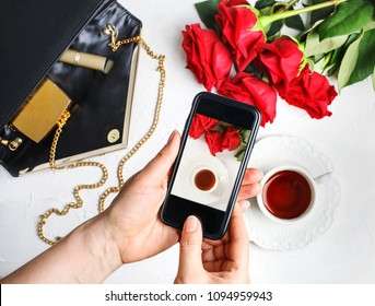Woman using smartphone to take photos of roses and cup of tea, top view