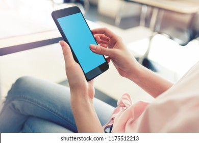 Woman using smartphone while sitting at a cafe. Closeup shot from a behind.