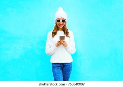 woman is using smartphone in white sweater, hat on a blue background in the city