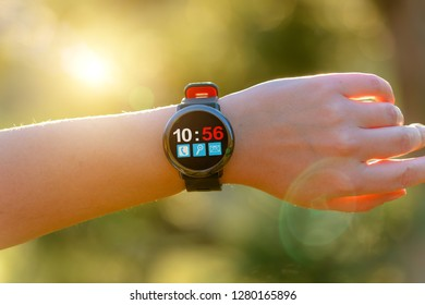 Woman using smartwatch with her finger, photo taken outdoors
