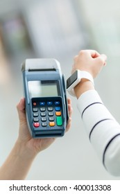 Woman using smartwatch for pay the bill