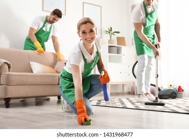 Woman using sponge and detergent for floor cleaning with her team in living room