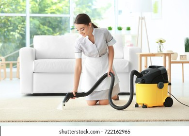Woman using steam vapor cleaner in living room