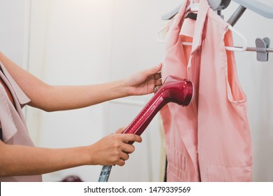 Woman using steaming iron to ironing fashion shirt in laundry room. Girl doing stream vapor iron for press clothes in hand. Launder concentrate work and delivery to customer. Part time job occupation