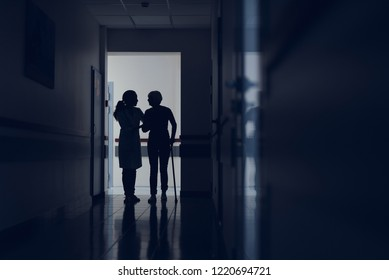 Woman is using stick for moving in clinic. Attentive practitioner is supporting her by hand while walking in corridor. Copy space in right side
