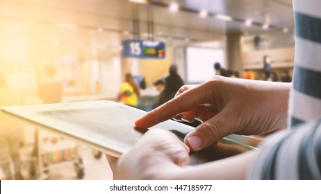 woman using tablet at airport terminal.