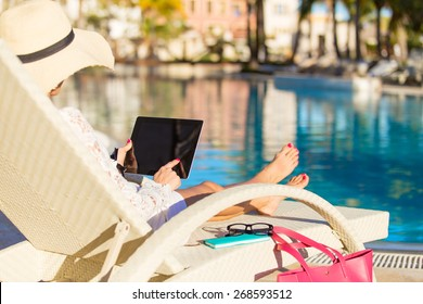 Woman using tablet computer on vacation in luxury resort