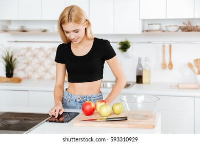 Woman using tablet computer and standing in kitchen