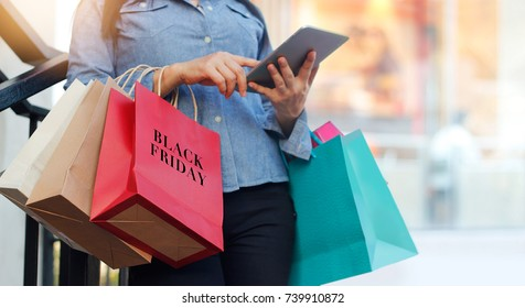 Woman using tablet and holding Black Friday shopping bag while standing on the stairs with the mall background