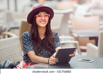 Woman using tablet on lunch break in city cafe outdoors. Portrait of young smiling girl sitting with tablet pc and smartphone and looking at camera