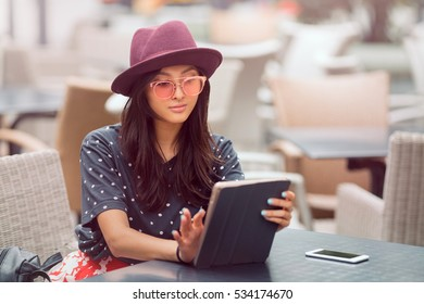 Woman using tablet on lunch break in city cafe outdoors. Young girl sitting with tablet pc and smartphone.
