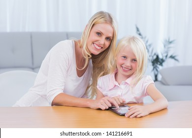 Woman using tablet pc with her daughter in the living room