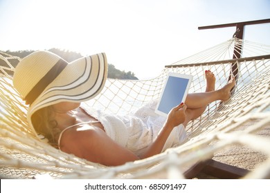 Woman using tablet pc on hammock