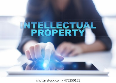 "Woman is using tablet pc, pressing on virtual screen and select ""Intellectual property""."