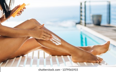 Woman using tanning cream to her legs near the swimming pool. Female sitting on a deck chair by the pool applying sunscreen lotion on to her legs.