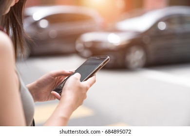 Woman using taxi app on mobile phone