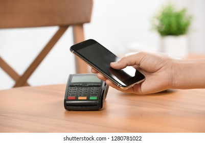 Woman using terminal for contactless payment with smartphone in cafe