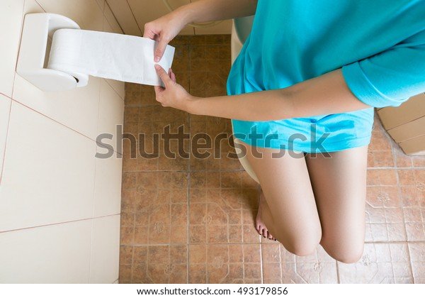 Woman using toilet paper  in the bathroom. view on top