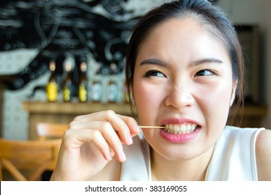 Woman using toothpick inside restaurant